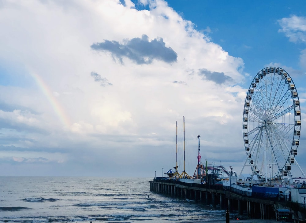ferris wheel near body of water under cloudy sky during daytime