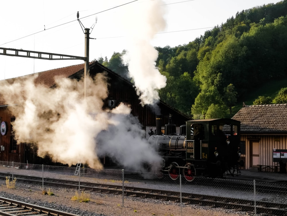 black train on rail tracks during daytime