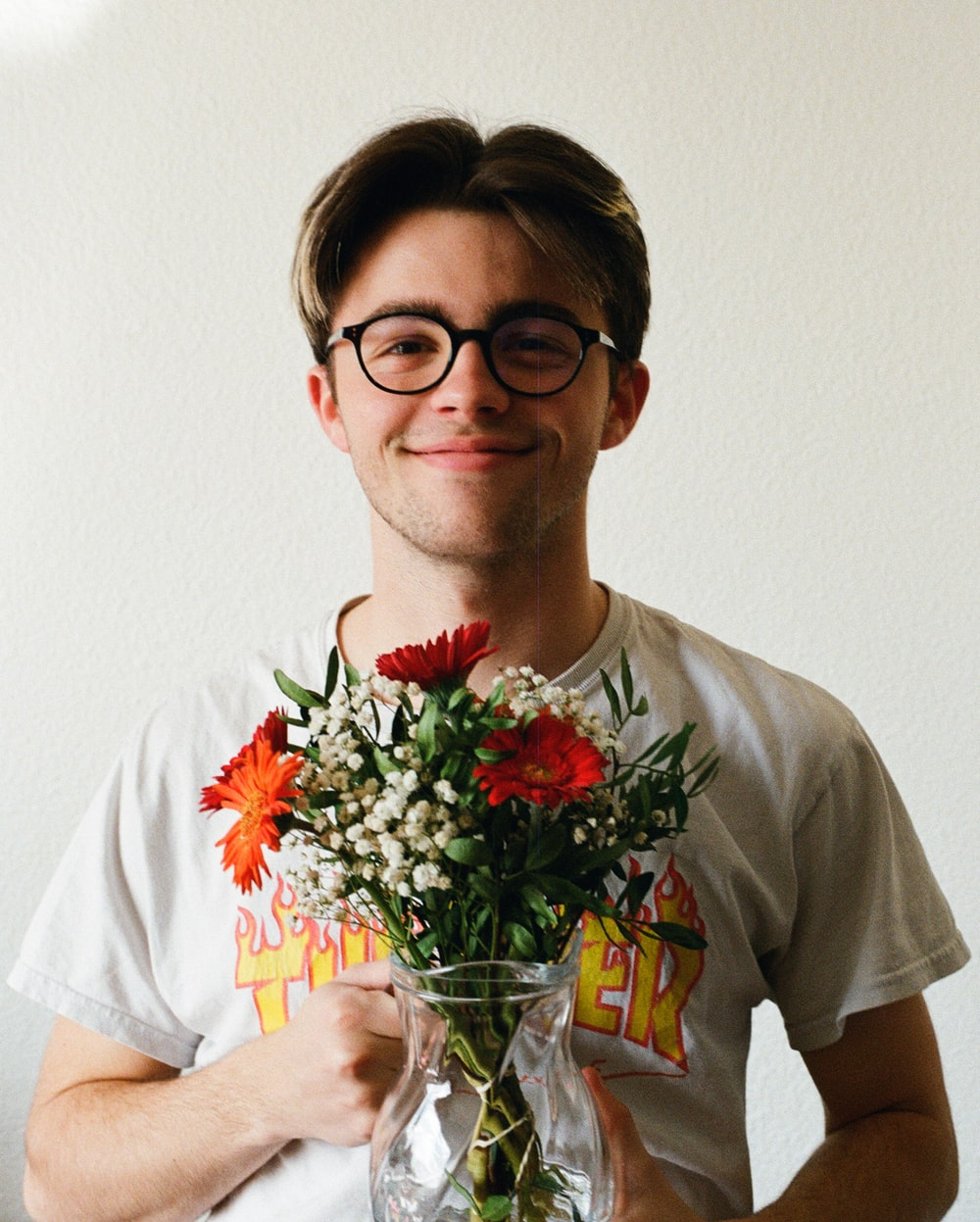 man in white crew neck t-shirt holding bouquet of red flowers