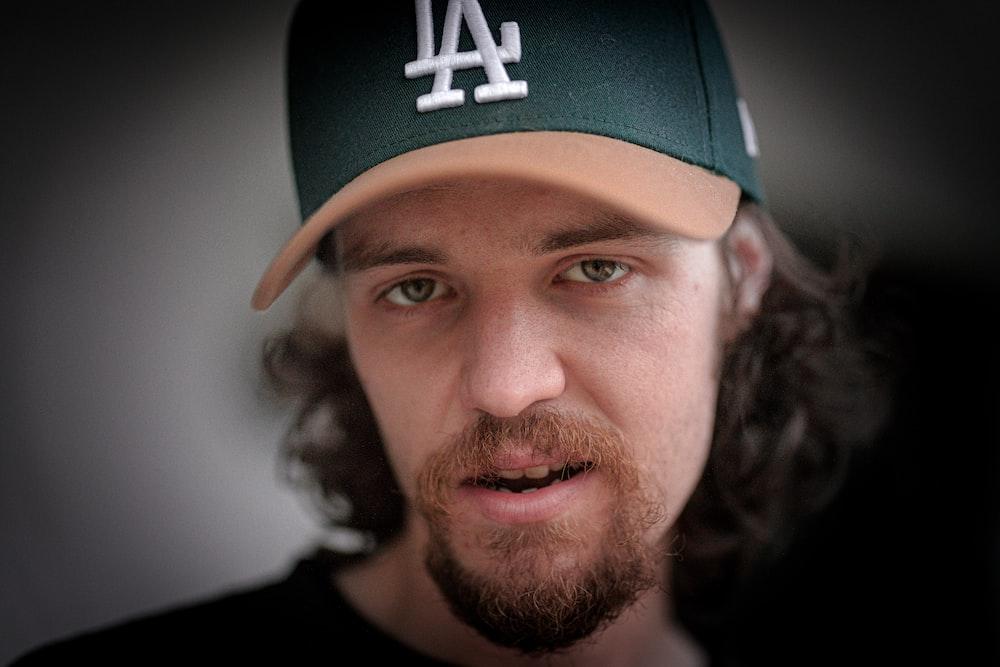 man in black crew neck shirt wearing green and white new york yankees cap