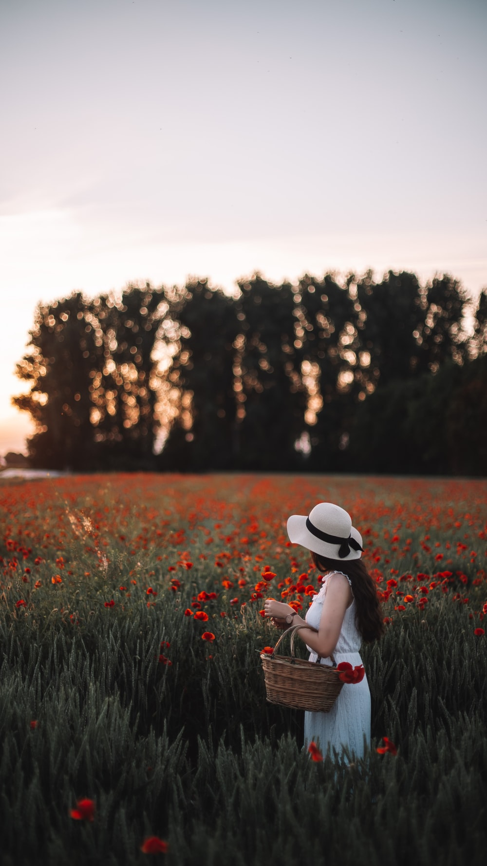 woman in white hat sitting on grass field during daytime