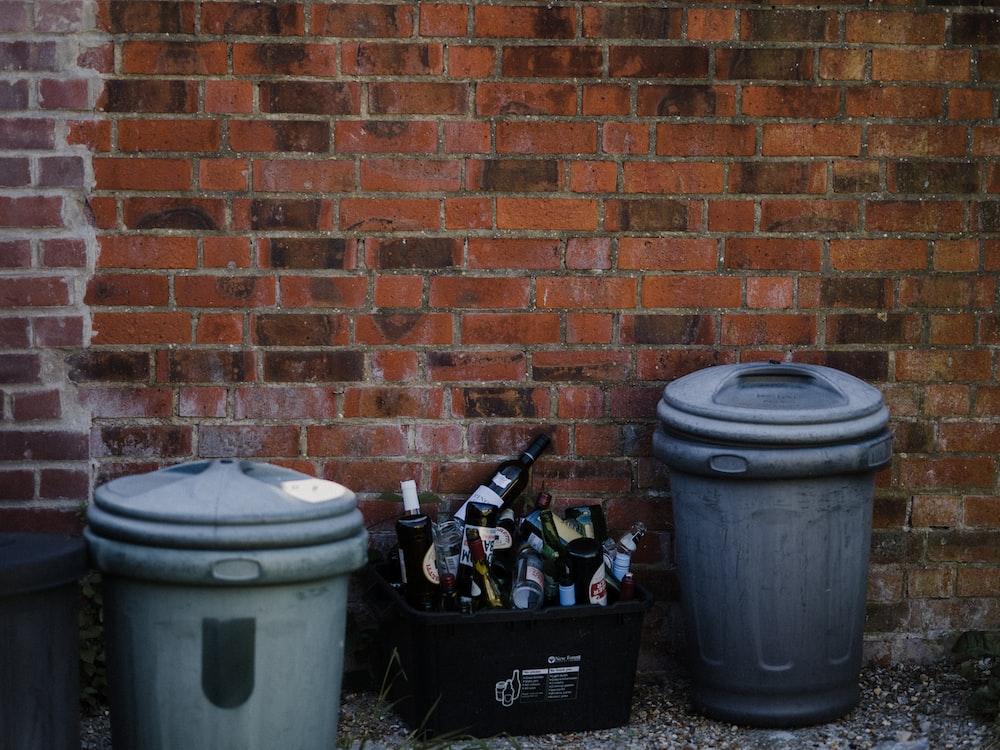 white plastic trash bin beside brown brick wall