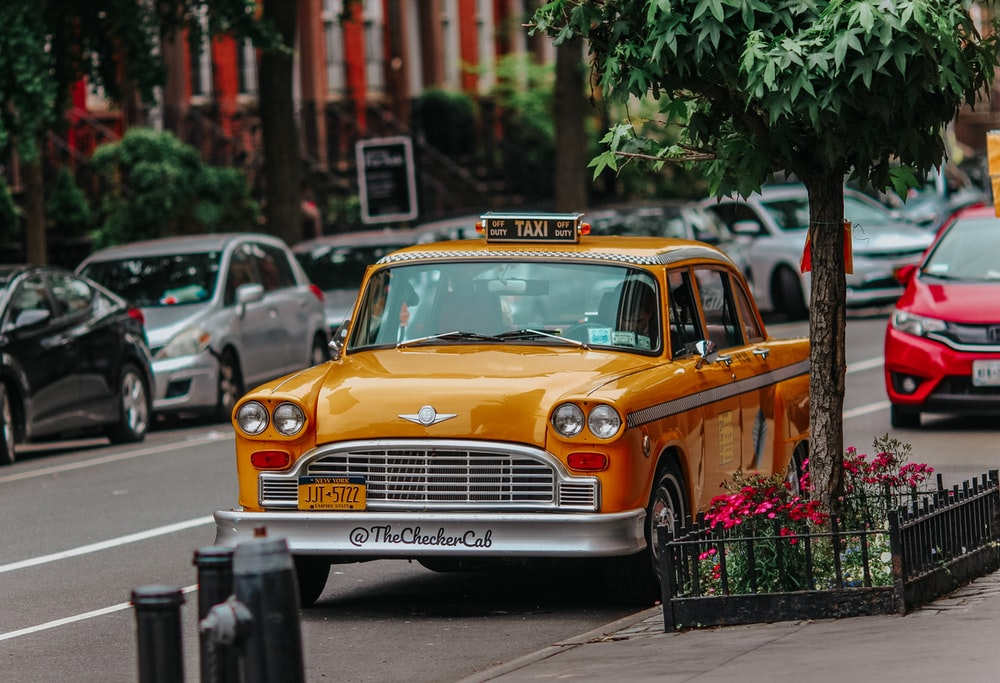 yellow taxi cab on the street during daytime