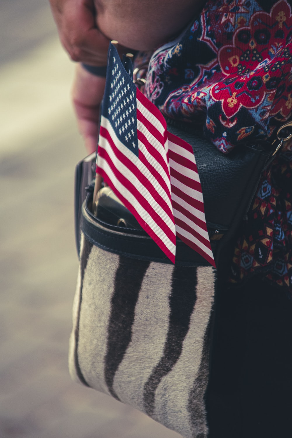 person in black red and white long sleeve shirt holding us flag