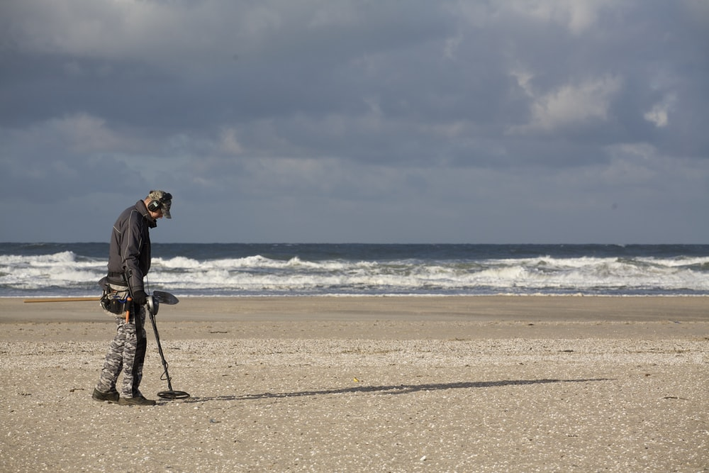 man in black jacket and black pants holding black dslr camera on beach during daytime