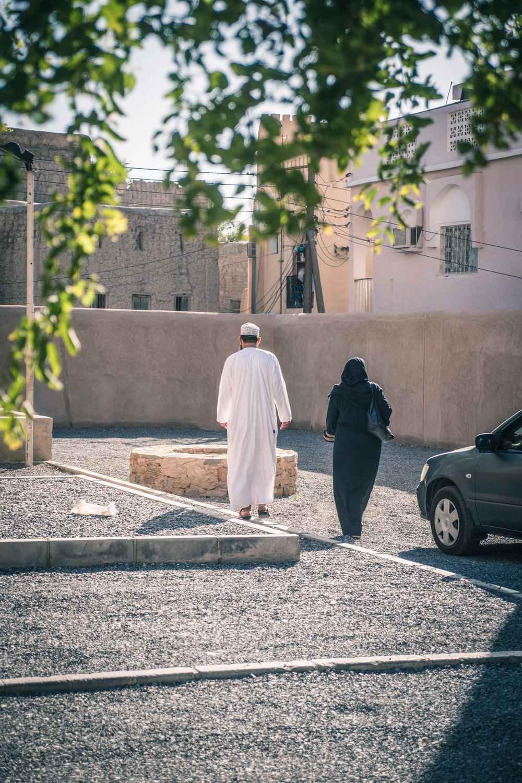 man in white thobe standing beside black car during daytime