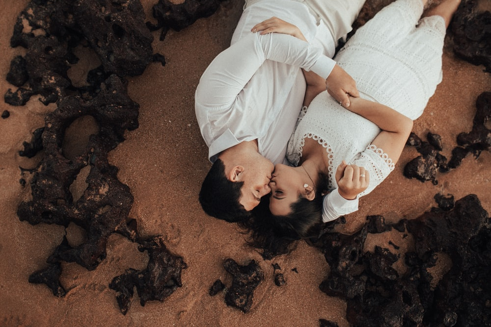 woman in white long sleeve shirt lying on brown sand