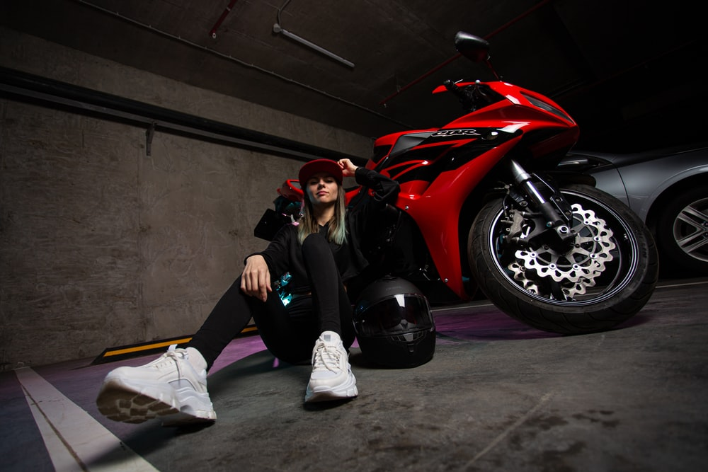 woman in black jacket and black pants sitting on red sports car