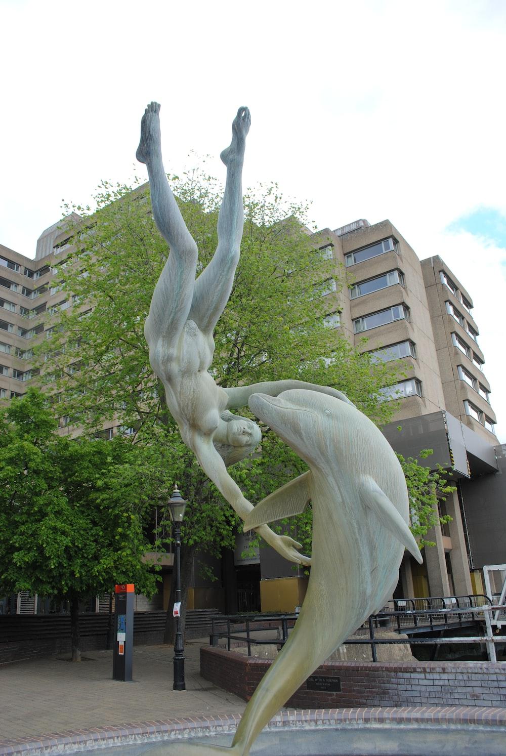 white concrete statue near brown concrete building during daytime