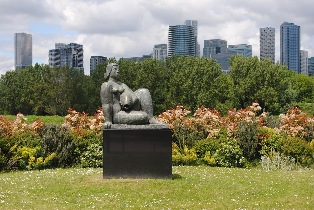 gray concrete statue on green grass field near green trees and high rise buildings during daytime