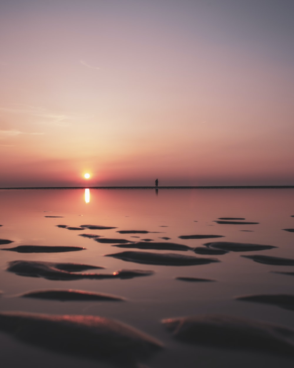 calm sea under gray sky during sunset