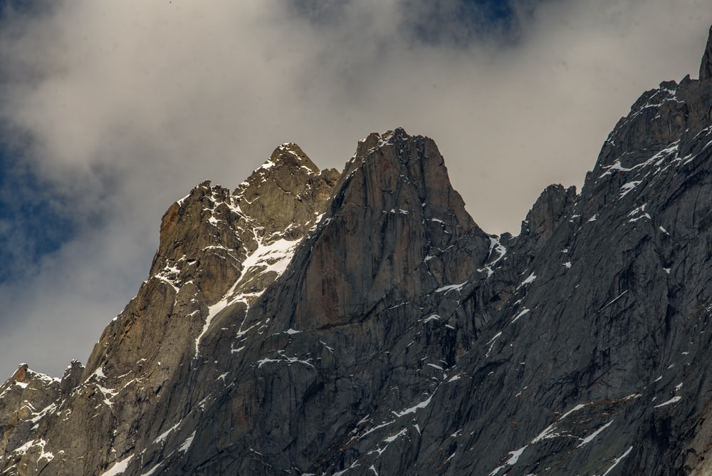 brown and gray rocky mountain under white clouds during daytime