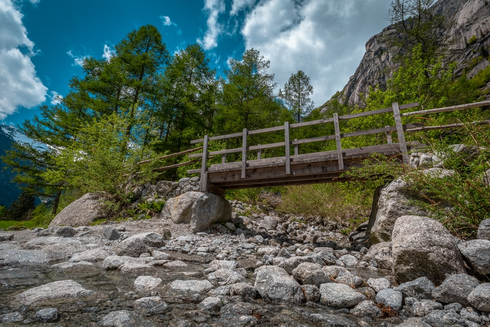 brown wooden bridge over rocky mountain during daytime