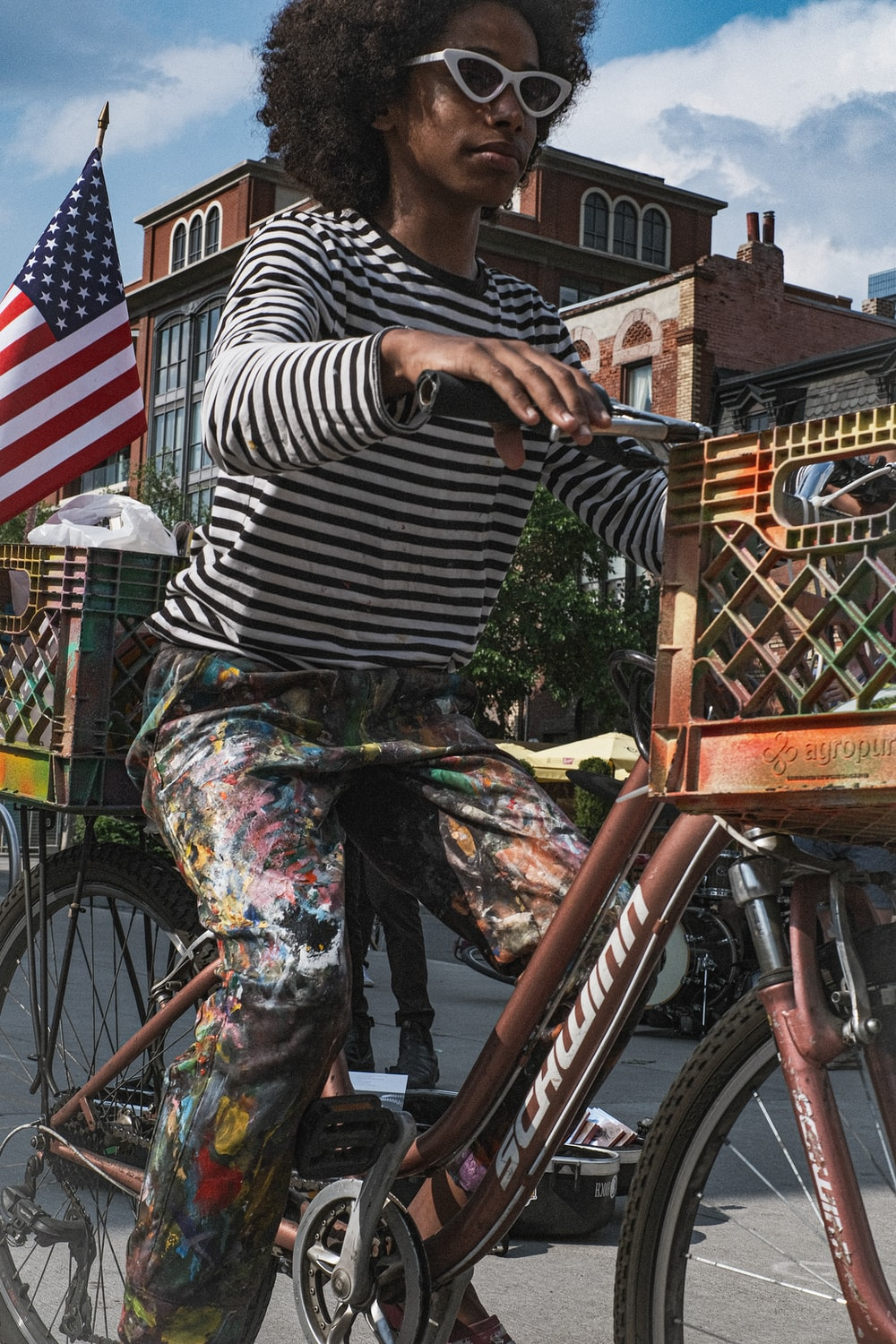 woman in black and white stripe shirt and gray pants riding on bicycle