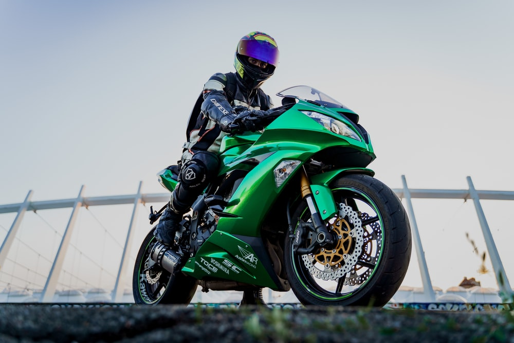 man in green and black motorcycle suit riding on green and black sports bike