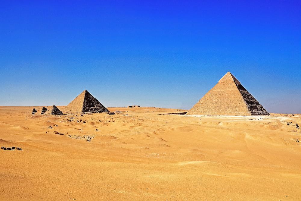 brown pyramid on desert under blue sky during daytime