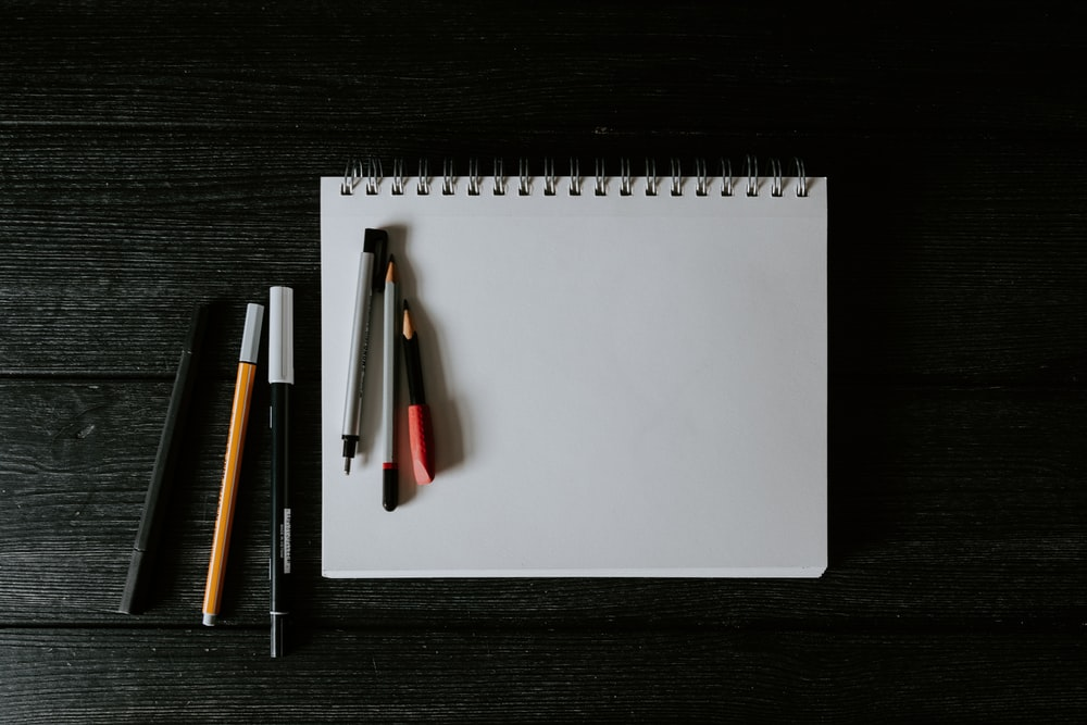white spiral notebook with black pen