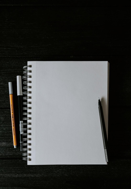 white spiral notebook beside orange pen