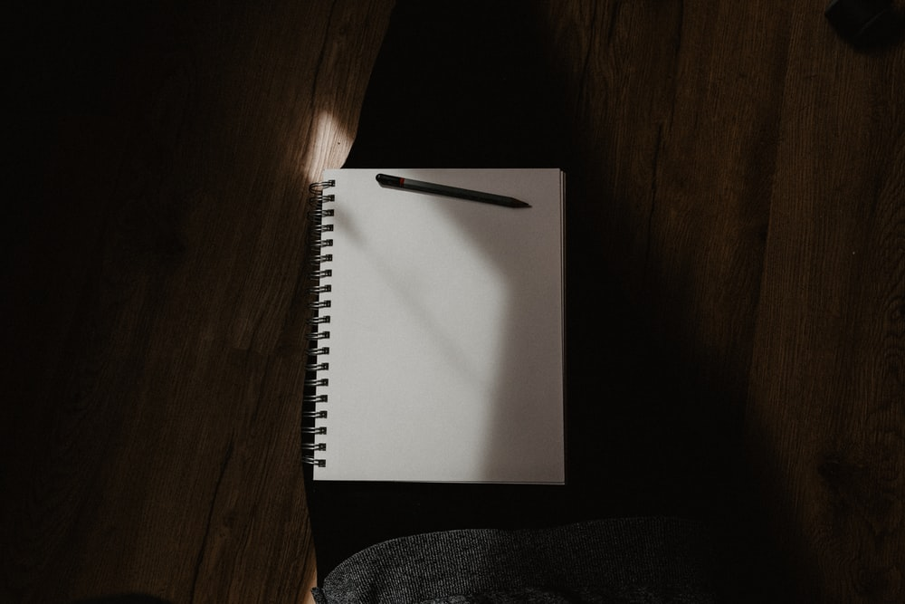 white spiral notebook on black textile
