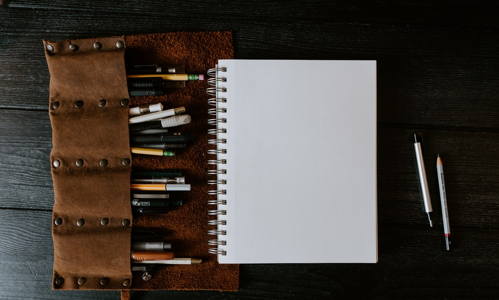 white spiral notebook on brown wooden table