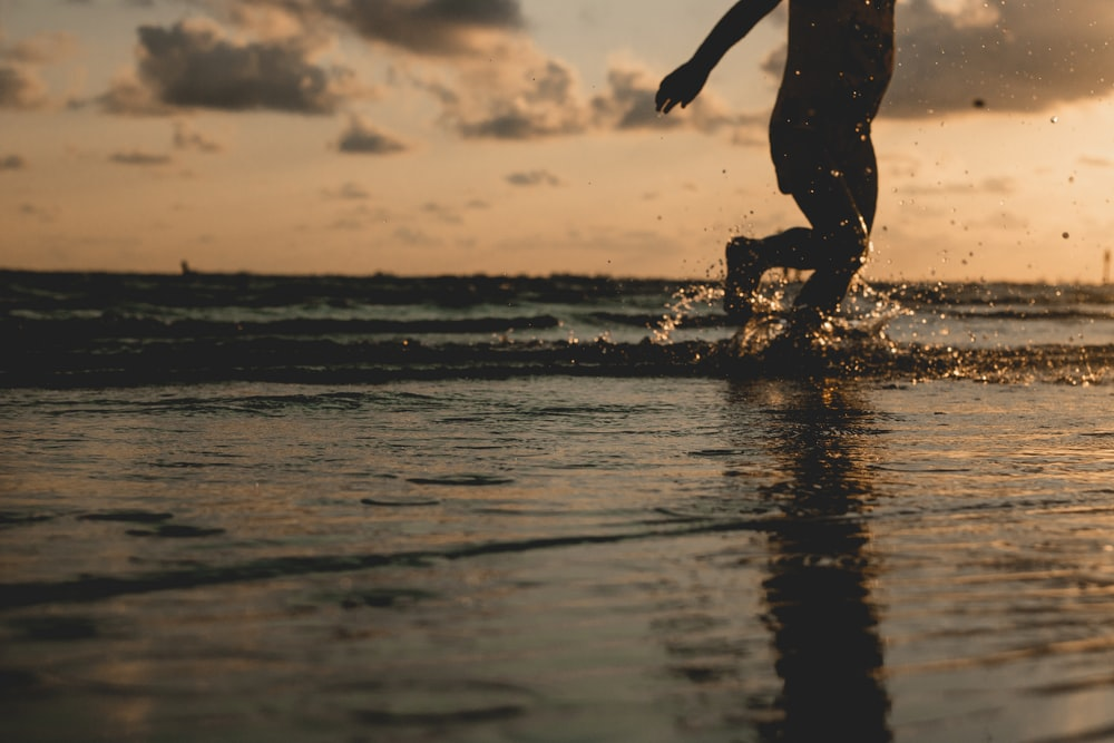 silhouette of person walking on water during sunset
