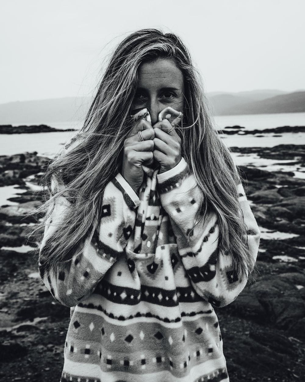 woman in black and white polka dot long sleeve shirt standing on seashore