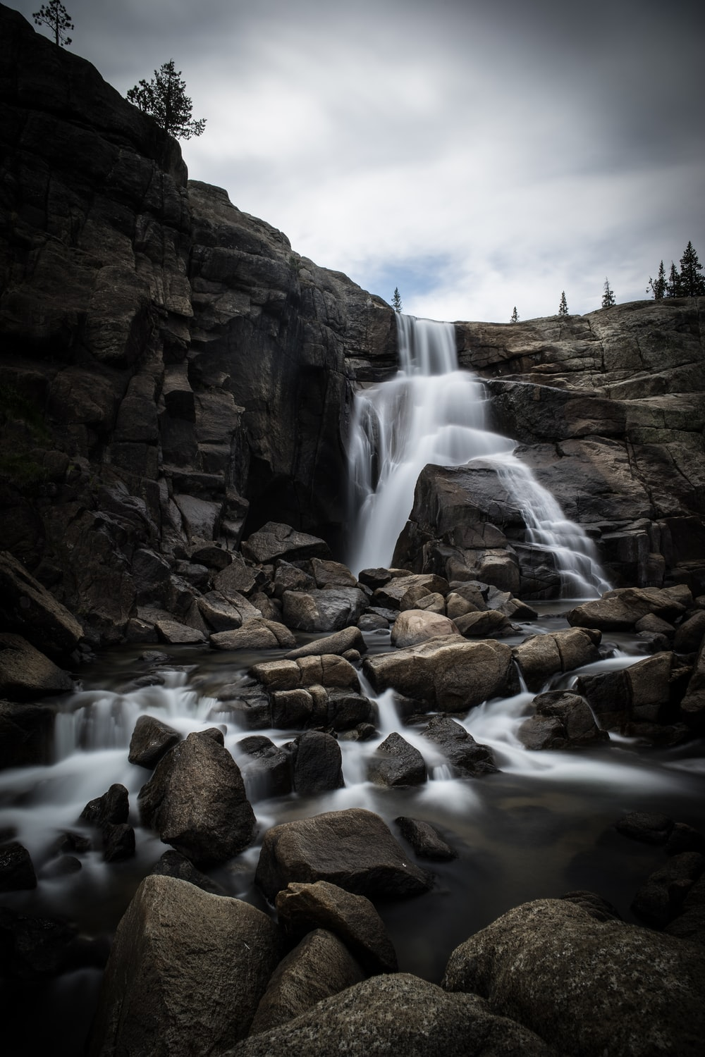 waterfalls on rocky mountain under cloudy sky during daytime