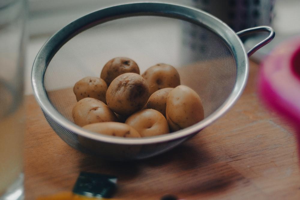brown round fruits on white ceramic bowl
