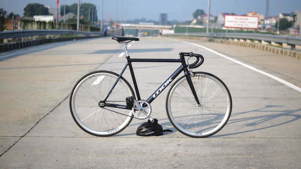 black and gray road bike on gray concrete road during daytime