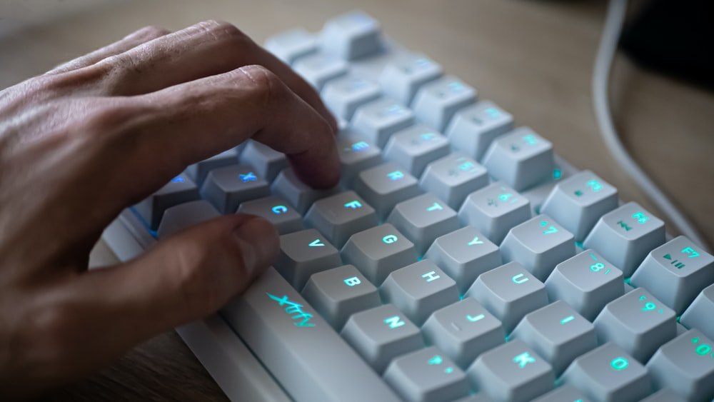 persons hand on white and blue computer keyboard