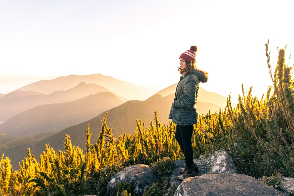 woman in green jacket standing on rock near yellow flower field during daytime