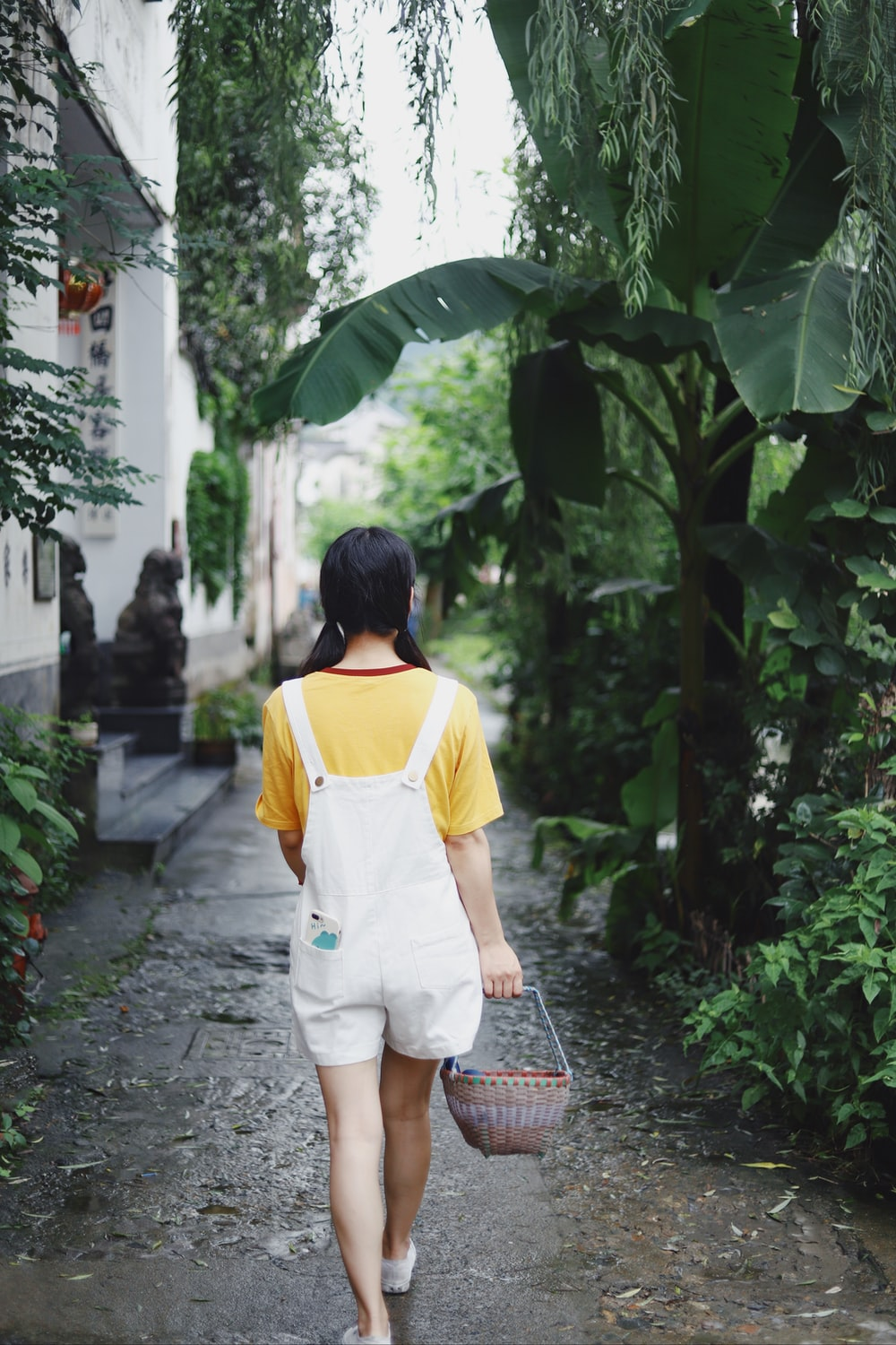 woman in white and yellow shirt walking on pathway