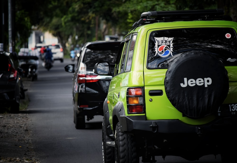 green and black jeep wrangler on road during daytime