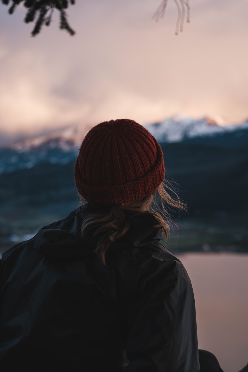 woman in black jacket and orange knit cap looking at the mountains during daytime