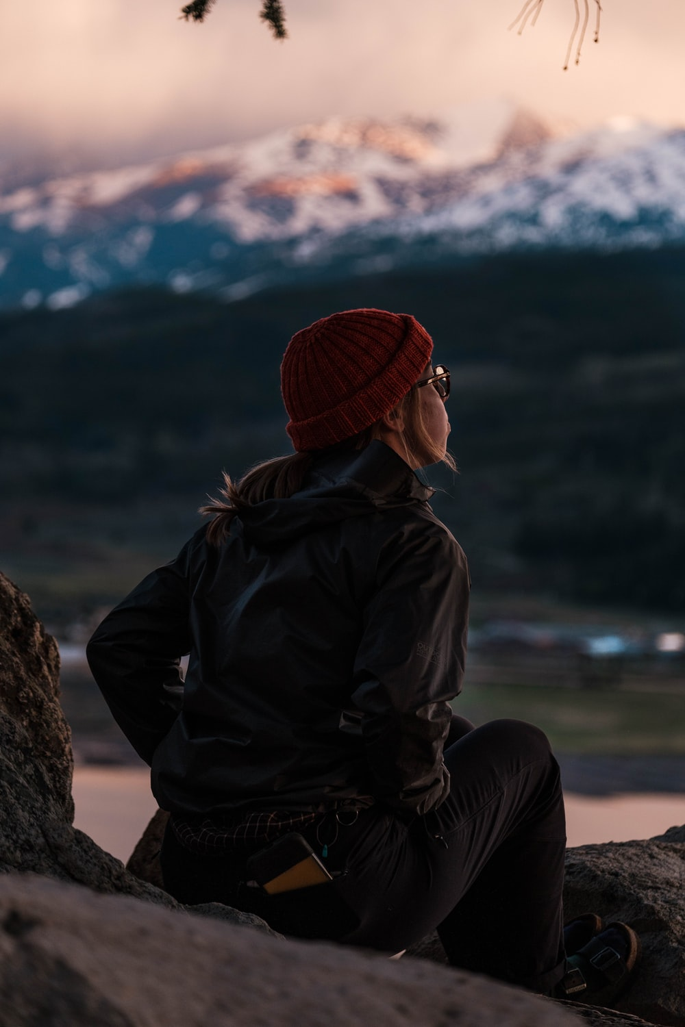 person in black jacket and red knit cap sitting on brown rock during daytime