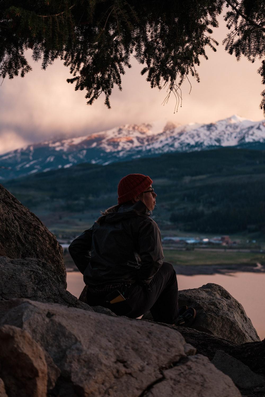 man in black jacket sitting on rock near body of water during daytime