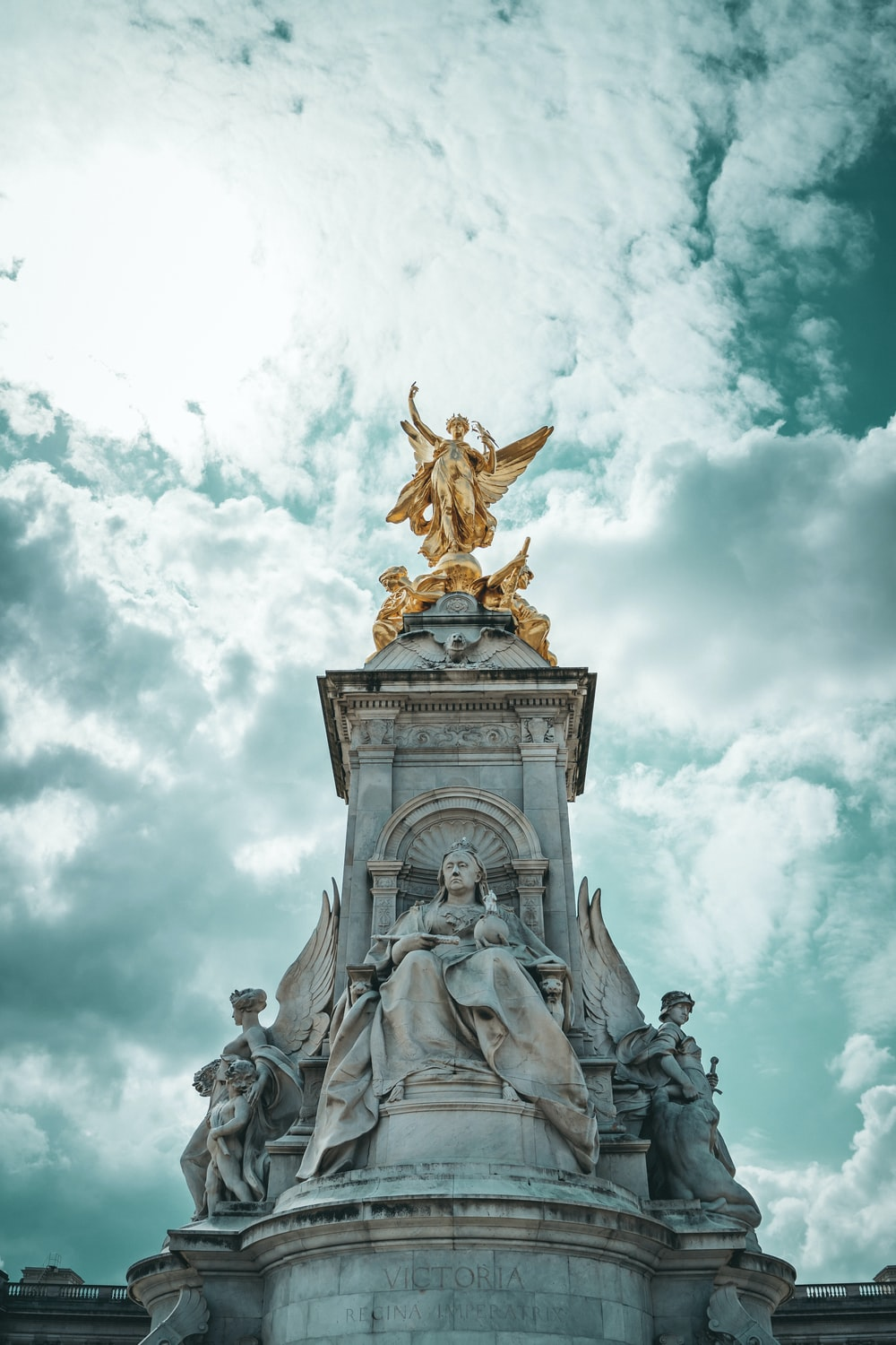 gold statue under cloudy sky during daytime