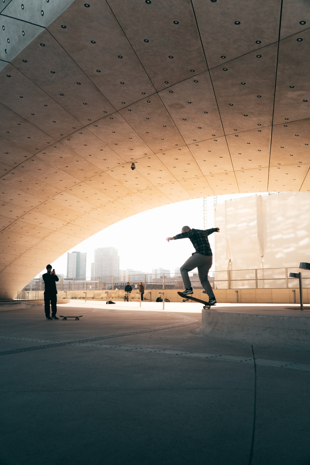 man in black jacket and black pants jumping on white concrete floor