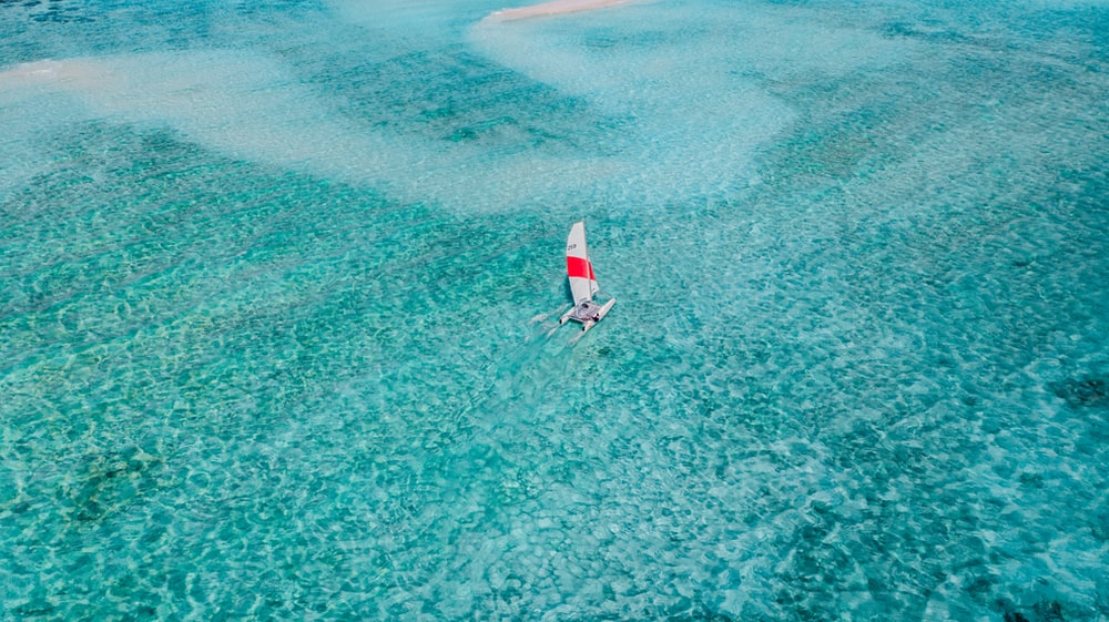 person in red shirt and blue shorts on white and red surfboard on body of water