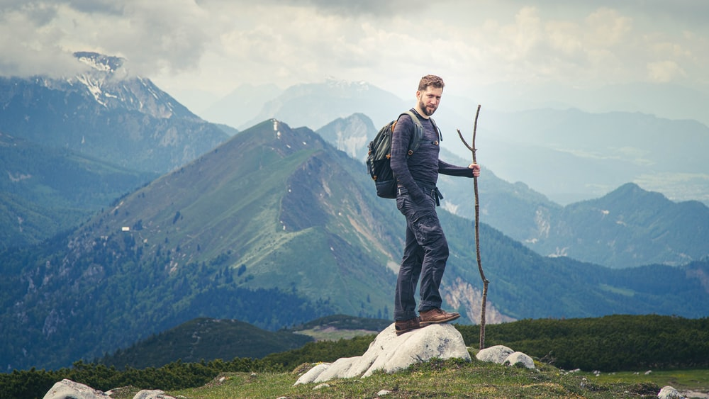 man in black jacket standing on rock