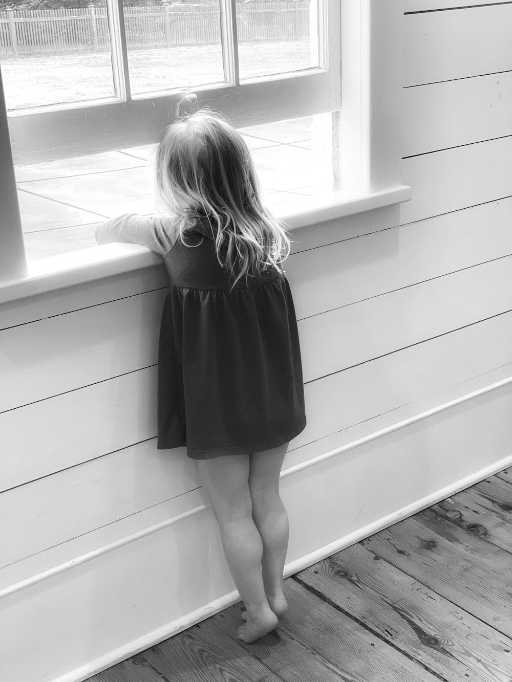 woman in black dress standing on wooden floor