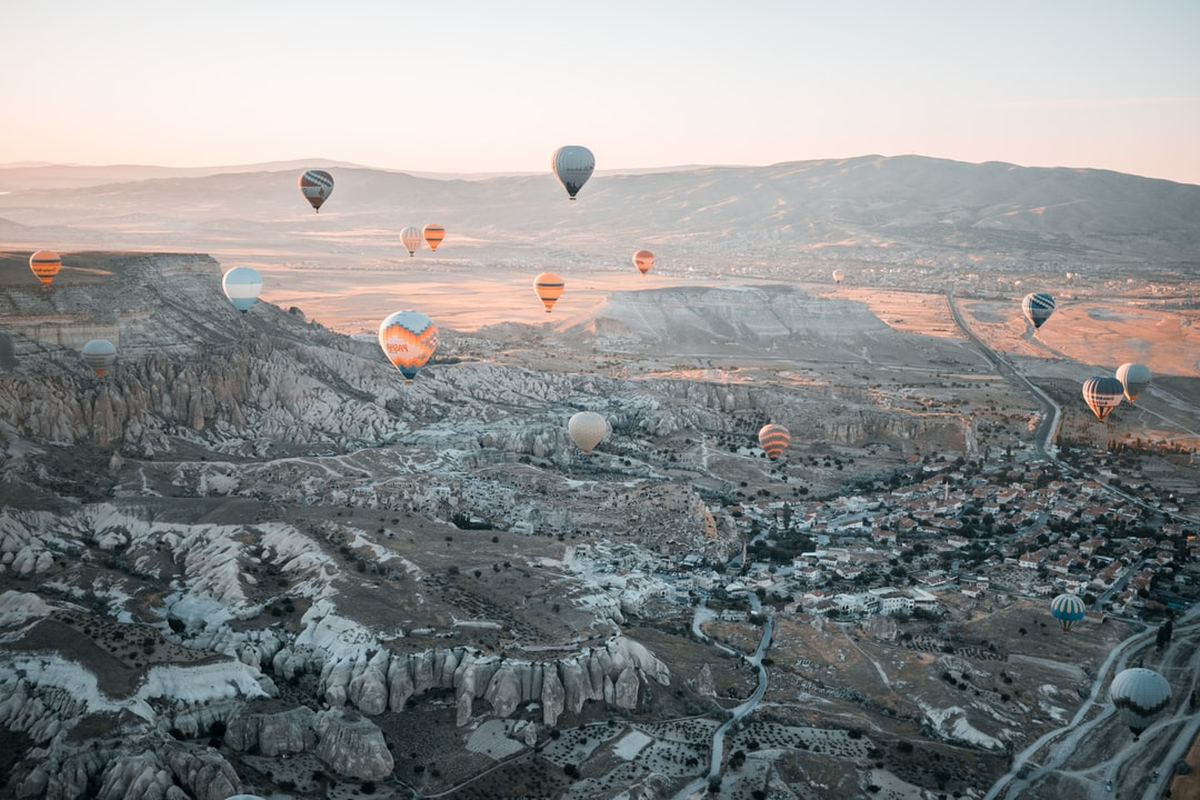 hot air balloons floating over the mountains
