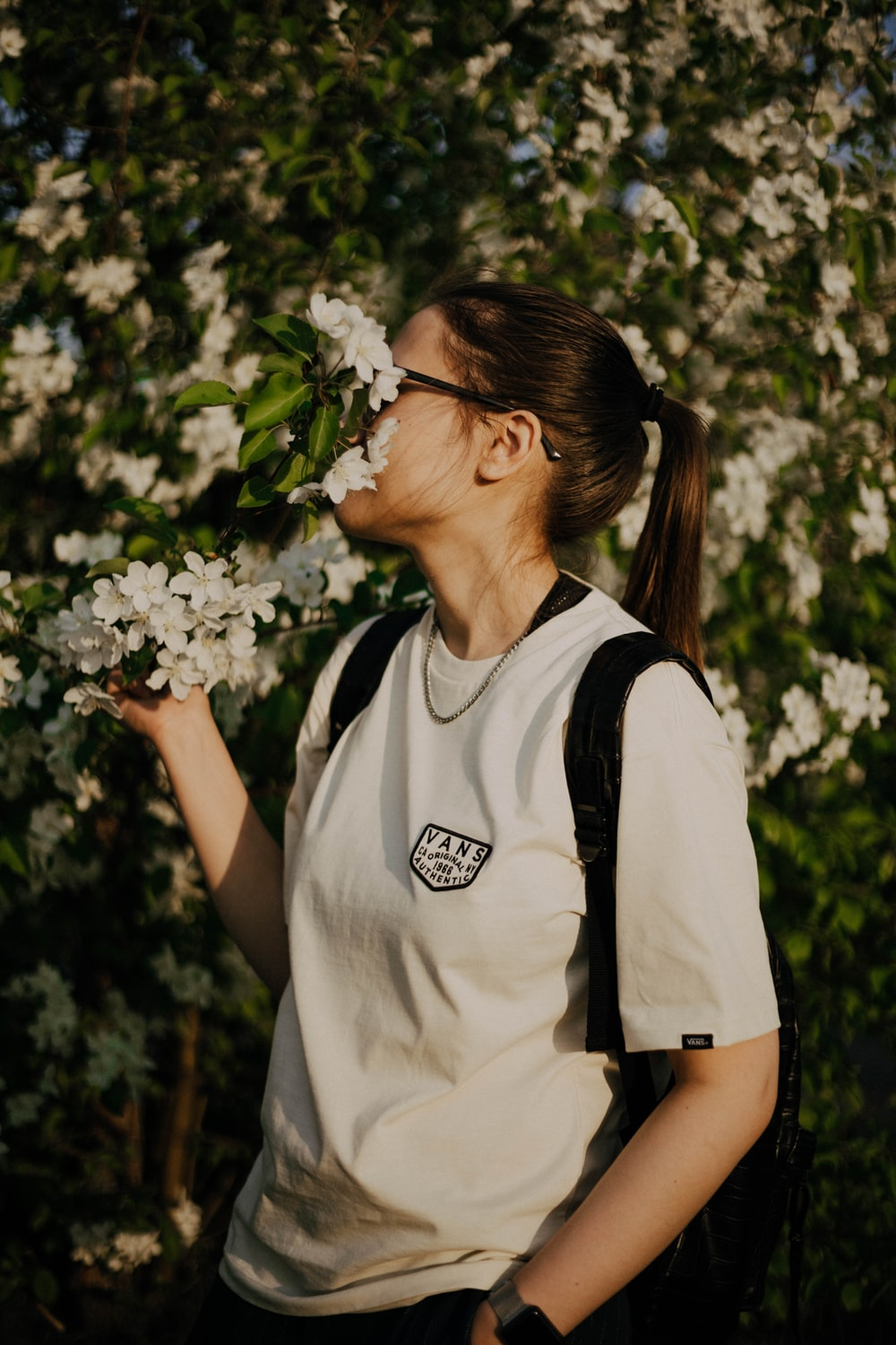 woman in white and black crew neck t-shirt holding white flowers