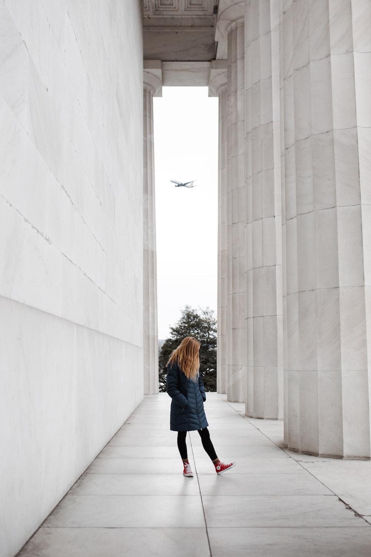 woman in blue long sleeve shirt and black pants walking on hallway