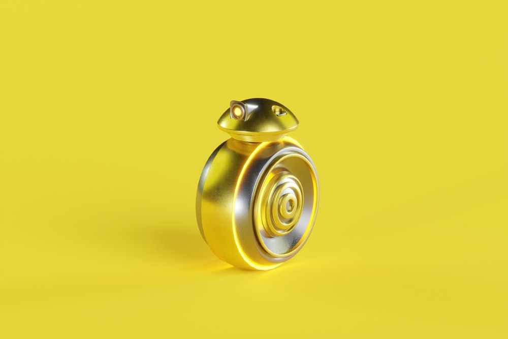 silver round ornament on yellow surface