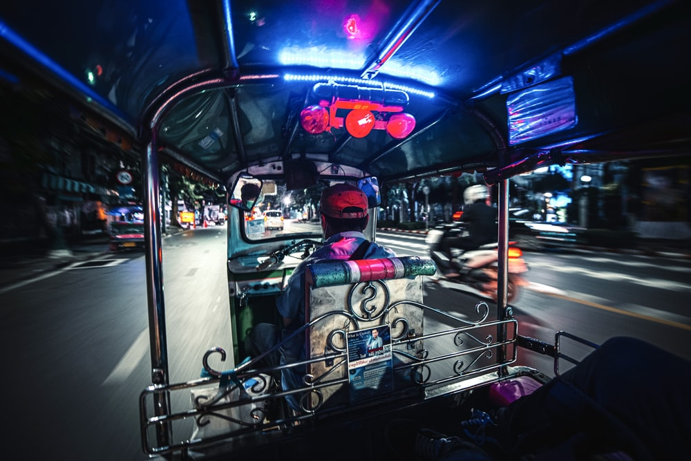people riding on blue and white car during nighttime