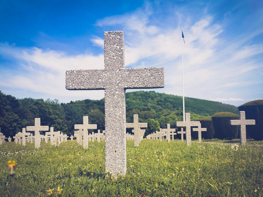 white cross on green grass field under blue sky during daytime