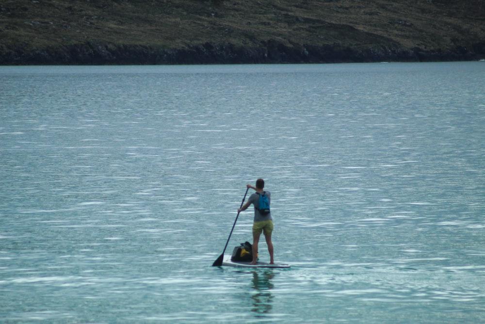 woman in yellow and black bikini riding on yellow kayak on blue sea during daytime