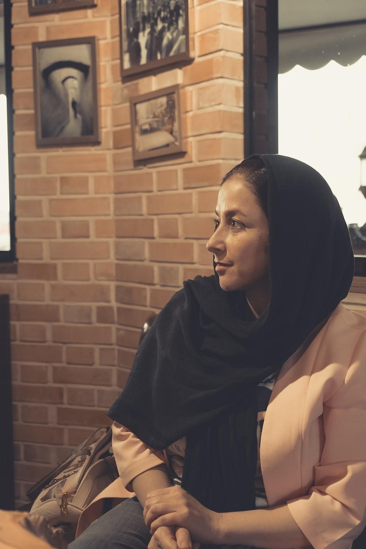 woman in black hijab sitting beside brown brick wall