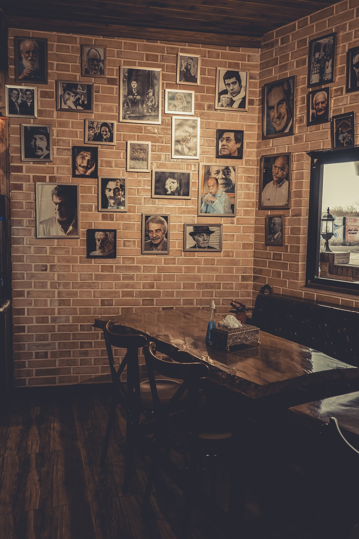 brown wooden table near black wooden framed wall art